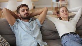 Couplez mettre des mains derrière la tête se reposant sur le divan se sent bien clips vidéos