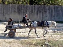 Couplez monter un cheval et un chariot dans le village Images stock