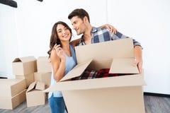 Couplez montrer des clés à la nouvelle maison et étreindre Photo stock