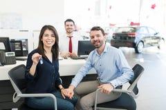 Couplez montrer leur excitation tout en achetant la première voiture photos stock