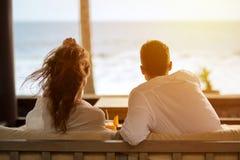 Couplez observer la mer de la terrasse de leur appartement Images libres de droits