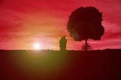 Couplez observer le coucher du soleil à côté d'un arbre et d'une bicyclette Photo stock