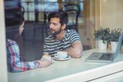 Couplez parler tout en se reposant par la fenêtre au café image stock