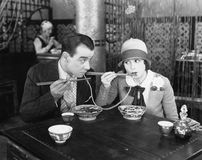Couplez partager une nouille dans un restaurant (toutes les personnes représentées ne sont pas plus long vivantes et aucun domain Images libres de droits