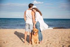 Couplez passer le temps ensemble sur la plage avec leur chien Photo stock