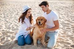 Couplez passer le temps sur la plage avec leur chien Photographie stock