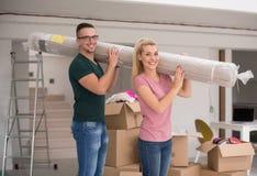 Couplez porter un tapis se déplaçant dedans à la nouvelle maison image libre de droits