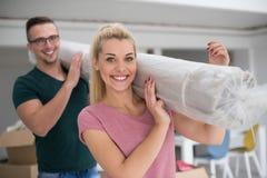 Couplez porter un tapis se déplaçant dedans à la nouvelle maison image stock