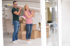 Couplez porter un tapis se déplaçant dedans à la nouvelle maison photo stock