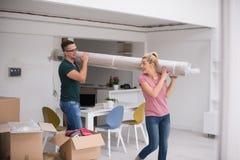 Couplez porter un tapis se déplaçant dedans à la nouvelle maison images libres de droits