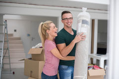 Couplez porter un tapis se déplaçant dedans à la nouvelle maison photographie stock