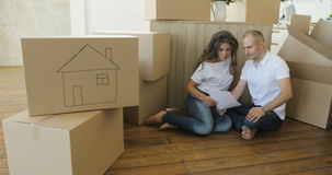 Couplez prévoir leur nouvel emplacement de salon sur le plancher jeune famille se déplaçant dans un nouvel appartement et des boî banque de vidéos