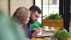 Couplez prévoir leur semaine utilisant un comprimé et un carnet se reposant dans un café banque de vidéos
