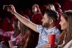 Couplez prendre l'autoportrait au téléphone intelligent dans le cinéma Photo libre de droits
