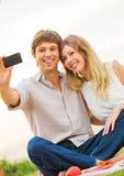 Couplez prendre la photo de lui-même avec le téléphone intelligent sur p romantique Image libre de droits