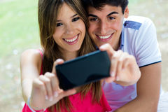 Couplez prendre la photo de lui-même avec le téléphone intelligent sur p romantique Photographie stock libre de droits