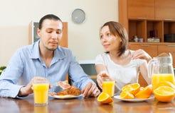 Couplez prendre le petit déjeuner avec les oeufs brouillés et les oranges Photo libre de droits