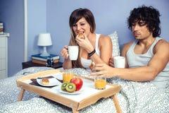 Couplez prendre le petit déjeuner dans le lit servi au-dessus du plateau Photo libre de droits