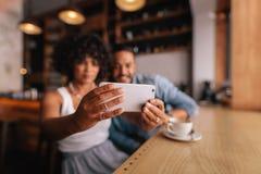 Couplez prendre le selfie avec le téléphone intelligent au café Photos stock