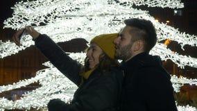 Couplez prendre le selfie et les baisers près de l'arbre de Noël dehors la nuit clips vidéos