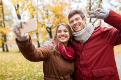 Couplez prendre le selfie par le smartphone en parc d'automne Image libre de droits