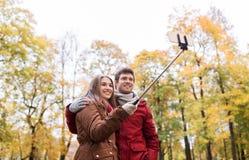 Couplez prendre le selfie par le smartphone en parc d'automne Photo stock