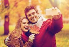 Couplez prendre le selfie par le smartphone en parc d'automne Images stock