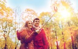 Couplez prendre le selfie par le smartphone en parc d'automne Photographie stock