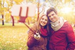 Couplez prendre le selfie par le smartphone en parc d'automne Photographie stock libre de droits