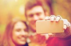 Couplez prendre le selfie par le smartphone en parc d'automne Photos stock