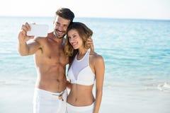 Couplez prendre le selfie tout en se tenant sur le rivage à la plage Photo libre de droits