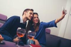 Couplez prendre un selfie avec un sittin de smartphone à la maison Images stock