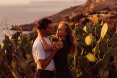 Couplez regarder des yeux aux yeux le soir sur le bord de la mer Images libres de droits