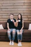 Couplez regarder l'appareil-photo et buvez du thé Images stock