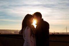 Couplez regarder l'un l'autre sur le dessus de toit au coucher du soleil image libre de droits
