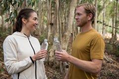 Couplez regarder l'un l'autre tenant la bouteille d'eau dans là des mains dans la forêt Images stock