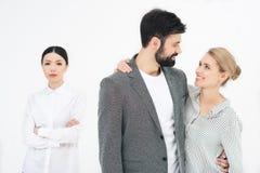 Couplez regarder l'un l'autre avec l'ami contrarié tout près Photo libre de droits
