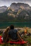 Couplez regarder l'un l'autre et la détente dans l'avant d'un beau lac de Suisse avec le feu à coté photo libre de droits
