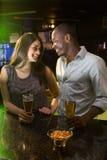 Couplez regarder l'un l'autre tout en ayant la bière au compteur de barre Photos libres de droits