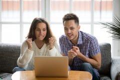 Couplez regarder le match de observation d'équipe de soutien d'écran d'ordinateur portable photographie stock libre de droits