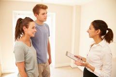 Couplez regarder un intérieur de maison avec un agent immobilier images libres de droits
