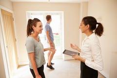 Couplez regarder un intérieur de maison avec un agent immobilier Photographie stock