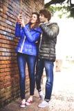 Couplez regarder un téléphone portable et une musique de écoute Image stock