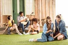 Couplez reposer et à l'aide du smartphone tandis que leurs amis jouant la guitare derrière Image libre de droits