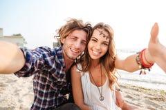 Couplez reposer et prendre le selfie sur la plage Photographie stock libre de droits