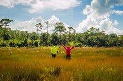 Couplez rester avec les mains augmentées à un champ de blé Images stock