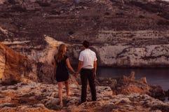Couplez rester le soir sur le bord de la mer Image libre de droits