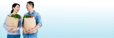 Couplez rire avec des sacs d'épicerie sur le fond bleu et blanc trouble Photographie stock libre de droits