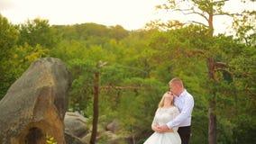 Couplez s'élever sur la roche et admirer le lever de soleil, le coucher du soleil clips vidéos