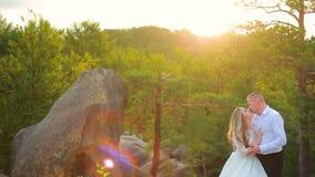 Couplez s'élever sur la roche et admirer le lever de soleil, le coucher du soleil banque de vidéos